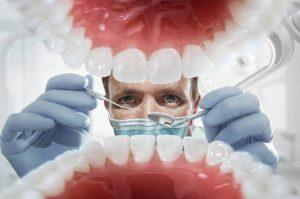 دندان پزشک در حال معاینه دندان های بیمار